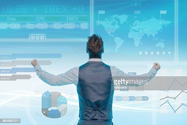Man looking at data on graphical screen, fists clenched, rear view