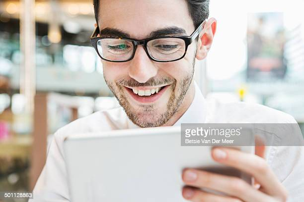 man looking at digital tablet, laughing.
