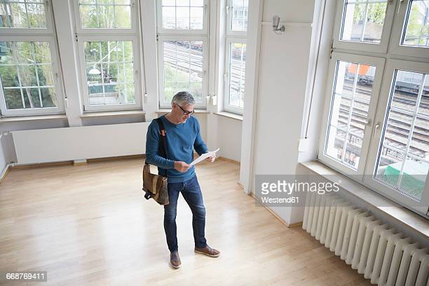 Man looking at document in empty apartment