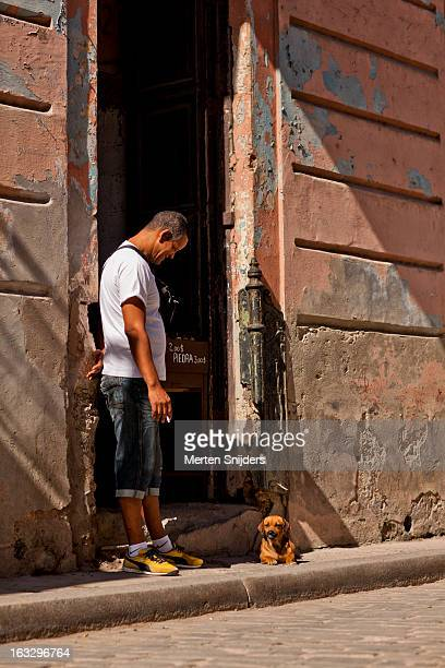 man looking at dog in doorway - merten snijders stock-fotos und bilder