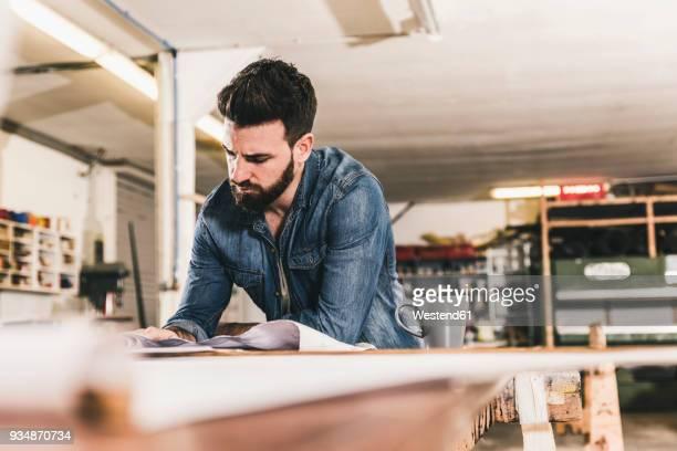 man looking at draft in workshop - kunsthandwerker stock-fotos und bilder