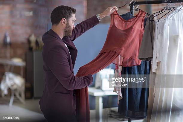 man looking at dress in boutique - man in dress stock photos and pictures