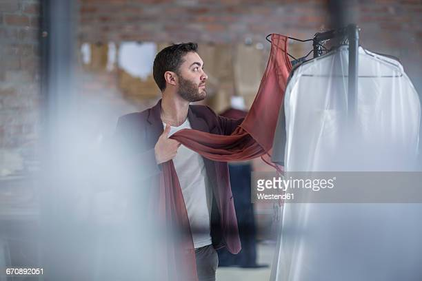 man looking at dress in boutique - fashion showroom stock pictures, royalty-free photos & images