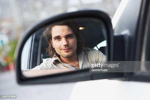 Man looking at driving mirror