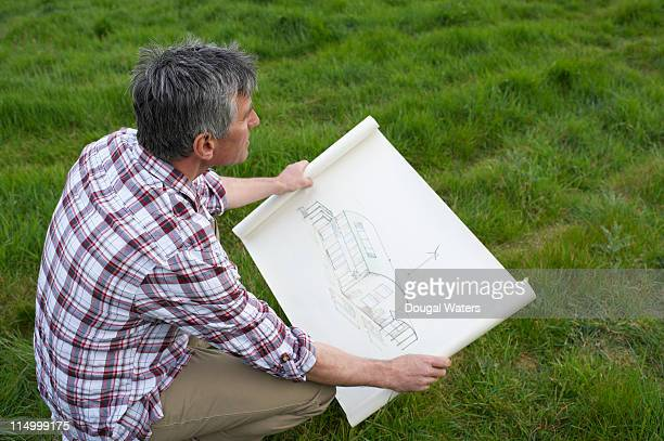 Man looking at eco build plan in field.