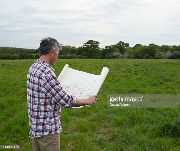 Man looking at eco build plans in field.