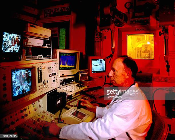 man looking at electron microscope - physicist stock pictures, royalty-free photos & images