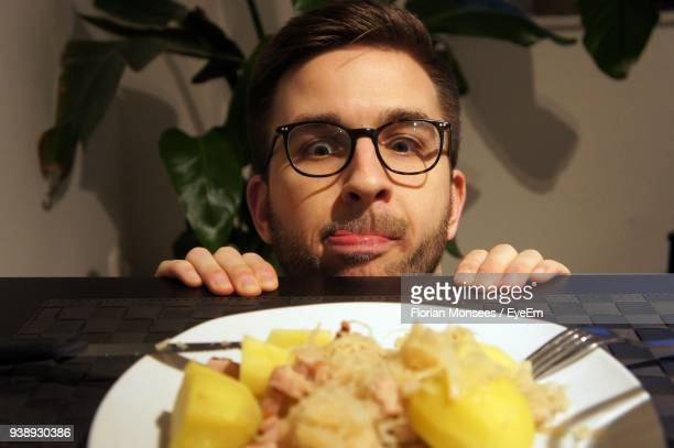 Man Looking At Food In Plate On Table