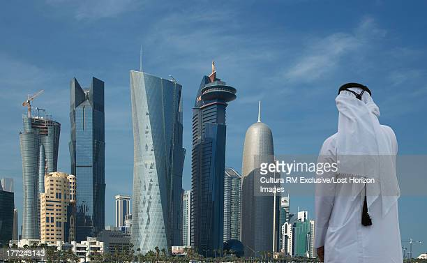 Man looking at futuristic skyscrapers of downtown Doha, Qatar