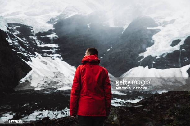 man looking at glacier and mountains in torres del paine national park - red coat stock pictures, royalty-free photos & images