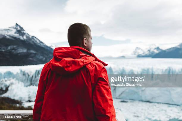 man looking at glacier perito moreno and mountains - glacier collapsing stock pictures, royalty-free photos & images