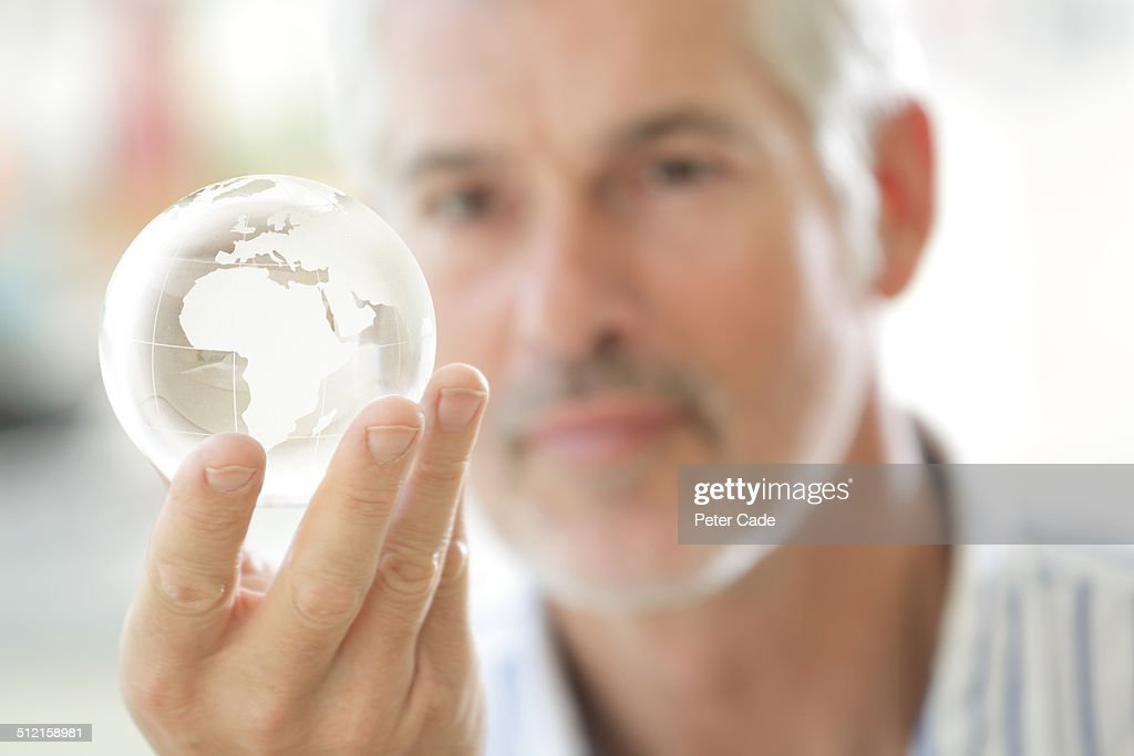 Man looking at glass globe : Stock Photo