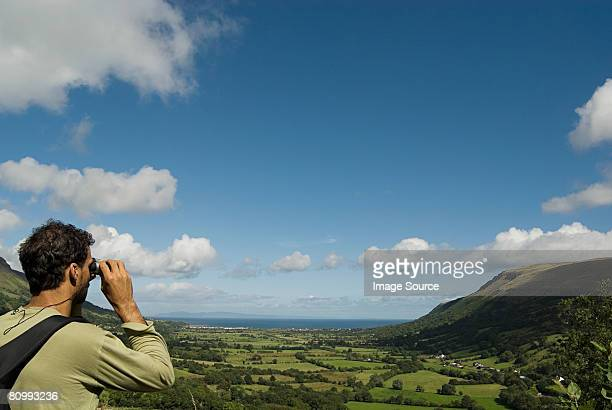 man looking at glenariff with binoculars - county antrim stock pictures, royalty-free photos & images