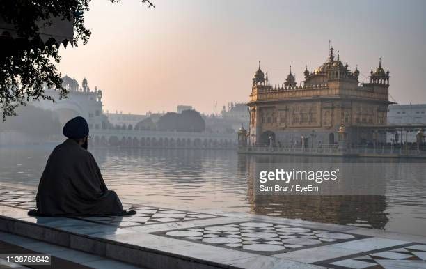 man looking at golden temple against sky during sunrise - amritsar stock pictures, royalty-free photos & images