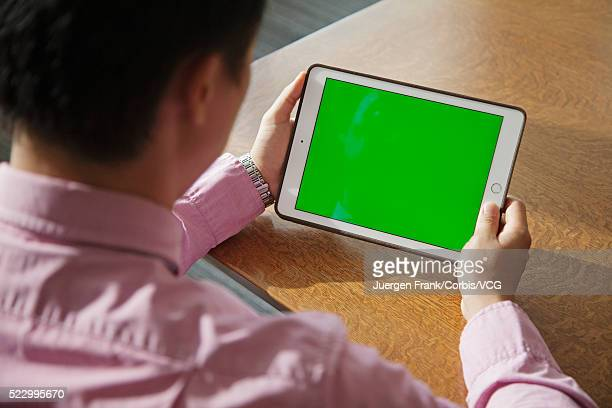 Man looking at green screen on his tablet