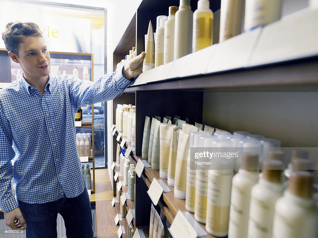 Man Looking at Hair Products in a Hair Salon : Stock Photo