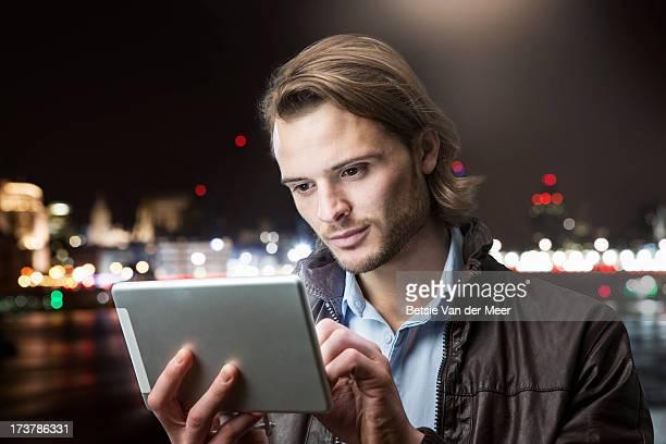 Man looking at hand held computer at night