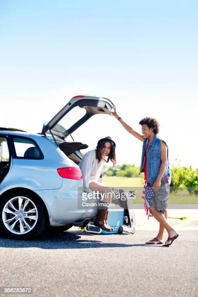 man looking at happy friend sitting in car trunk against clear sky - boot stock pictures, royalty-free photos & images