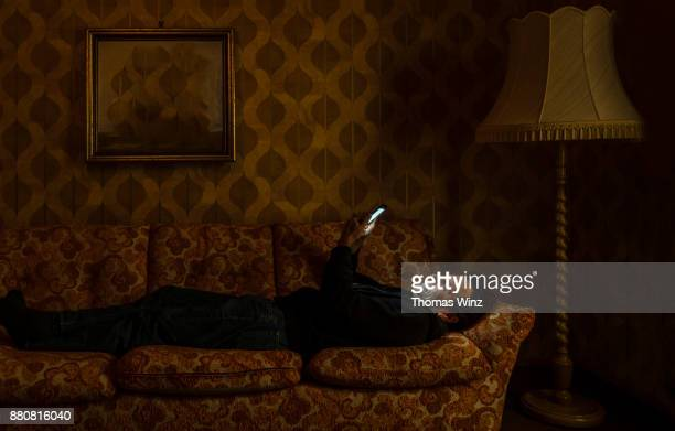 man looking at his cell phone on a couch - reclusão imagens e fotografias de stock