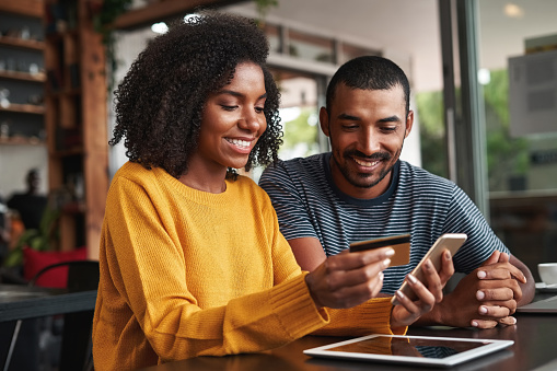 Man looking at his girlfriend shopping online in cafe 1159440600