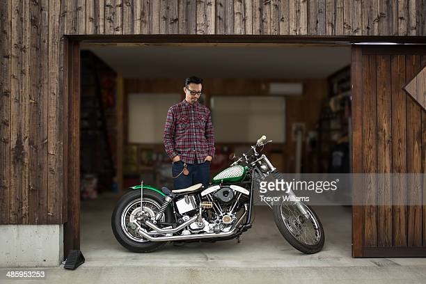 A man looking at his motorcycle in a garage