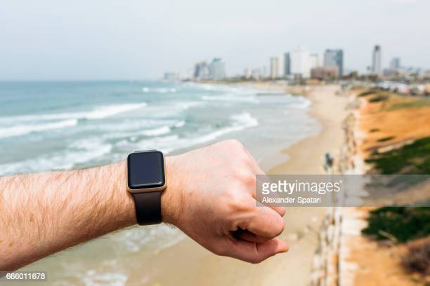 Man looking at his smart watch on the beach with city skyline in the background