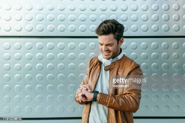 man looking at his watch in front of a silver wall - wrist watch stock pictures, royalty-free photos & images