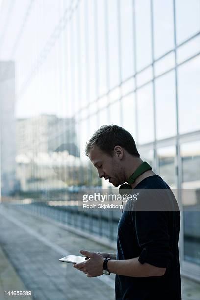 Man looking at Ipad with headphones around neck.