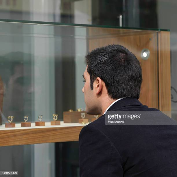 man looking at jewelry in shop window - jewellery products stock photos and pictures