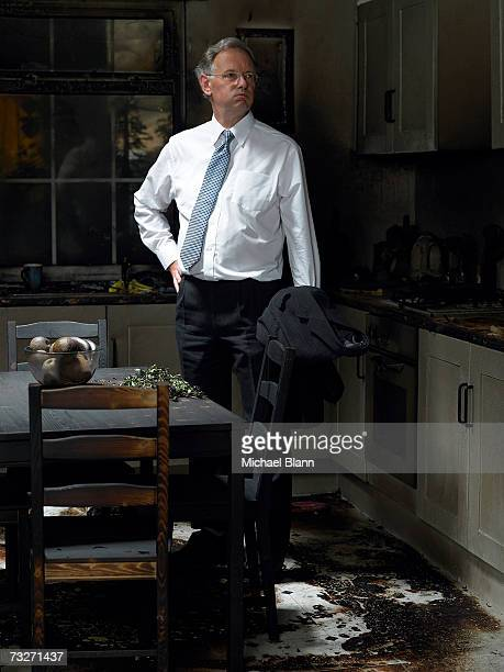 Man looking at kitchen damaged in fire