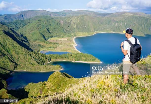 man looking at lagoa do fogo, sao miguel island, azores, portugal. - iacomino portugal foto e immagini stock