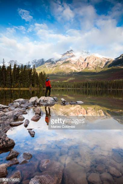 man looking at lake in autumn at sunrise, canada - canadian rockies stockfoto's en -beelden