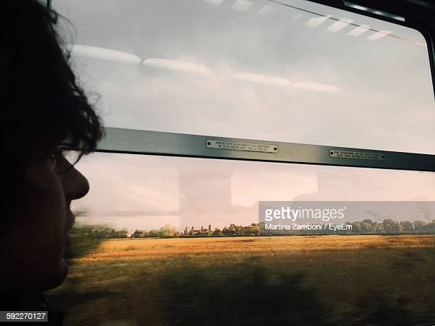 Man Looking At Landscape Through Train Window