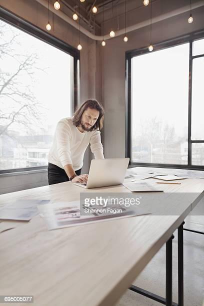 Man looking at laptop in office design studio