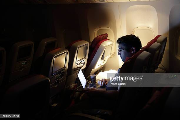 man looking at laptop, on an aircraft.