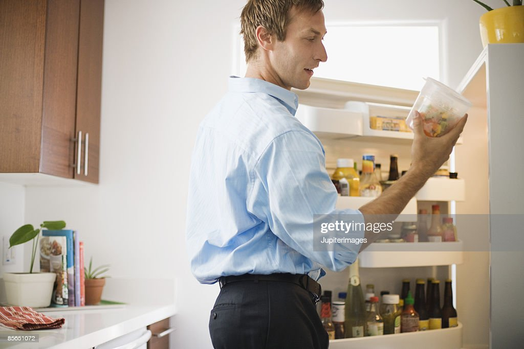Man looking at leftovers in refrigerator : Stock Photo