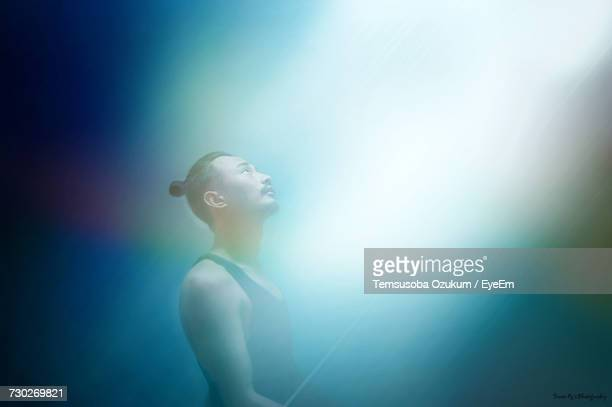 Man Looking At Light Against Blue Background