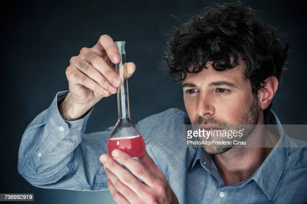 Man looking at liquid in conical flask