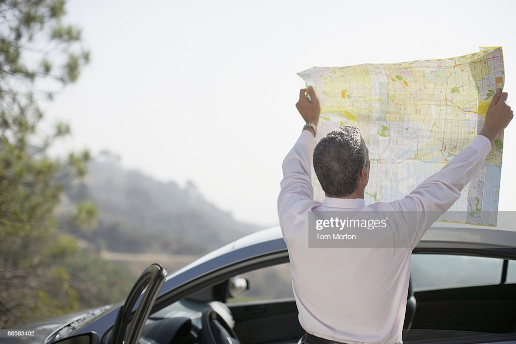 Man looking at map by car : Stock Photo