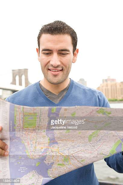 Man looking at map in front of Brooklyn Bridge