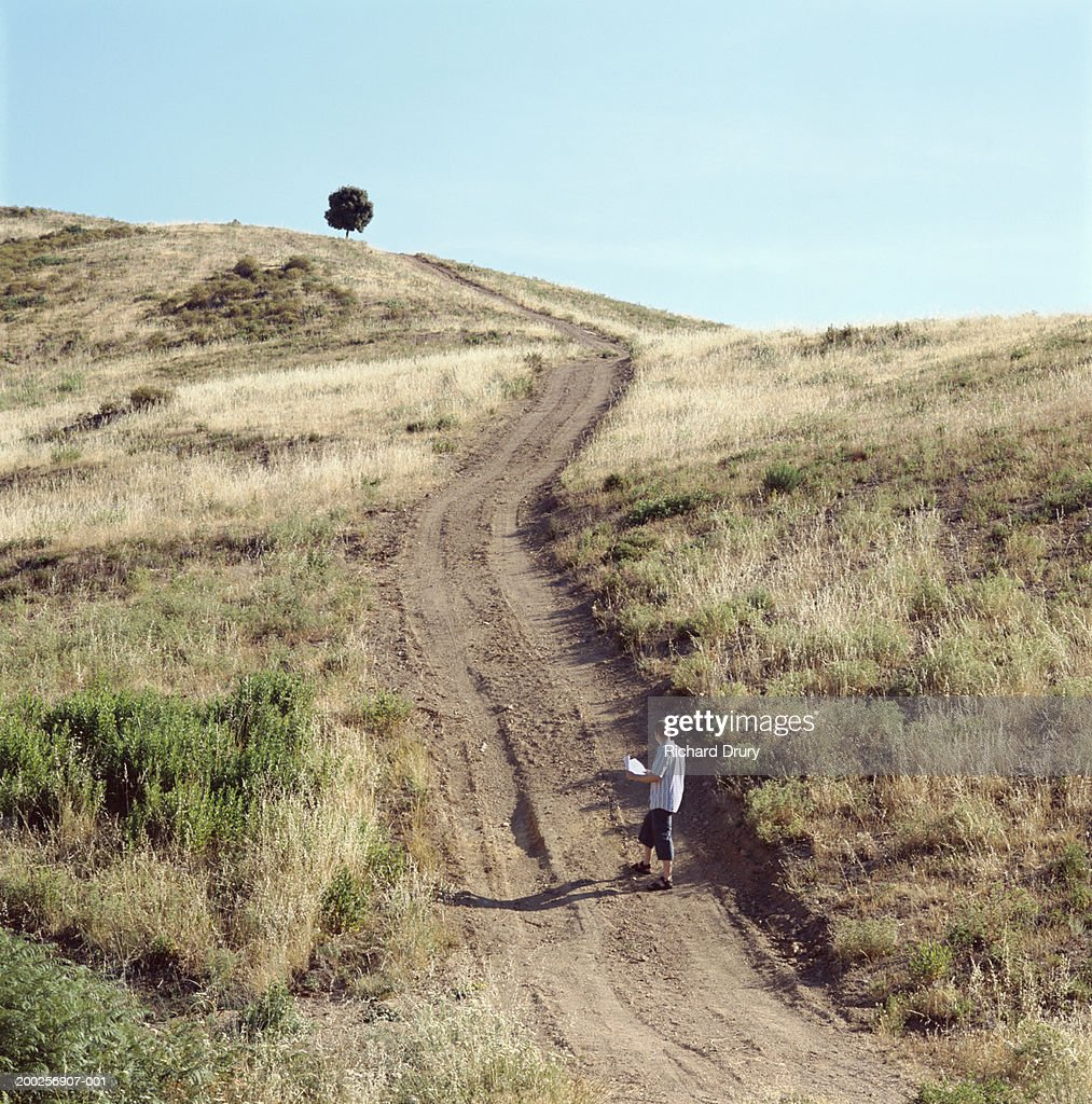 Man Looking At Map On Dirt Road At Foot Of Hill Stock-Foto - Getty on