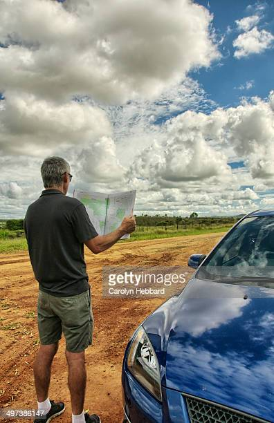 Man Looking at Map on Dirt Road