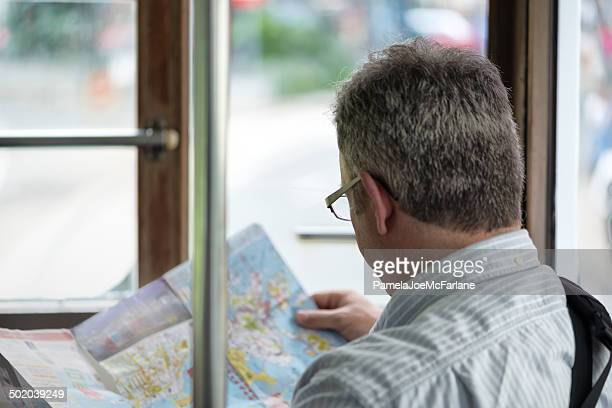 man looking at map while riding public transportation - lech stock pictures, royalty-free photos & images