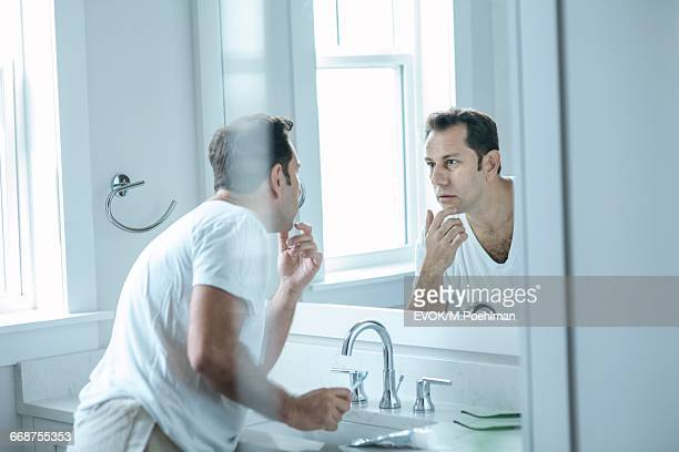 Man looking at mirror in bathroom