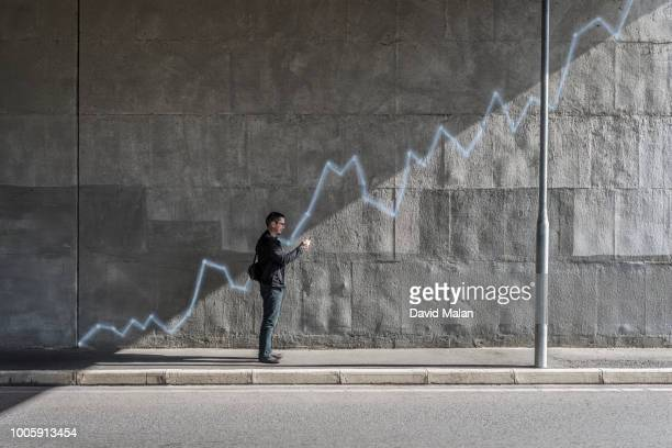Man looking at mobile device with a growth graph painted on the wall behind him.