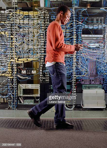 Man looking at mobile phone in front of computer server, side view