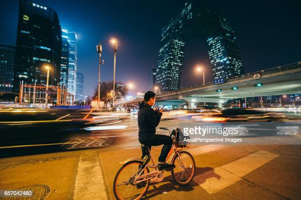Man Looking at Mobile Phone on a bike at Night