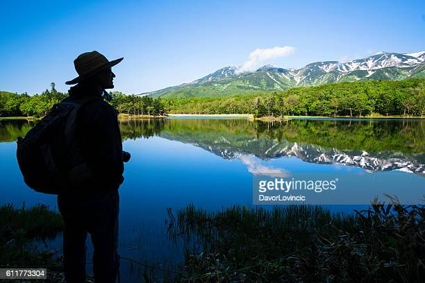 Man looking at Mountain reflection in Lake Yonko, Hokkaido, Japan