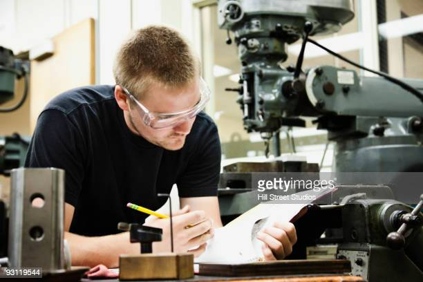 man looking at notes in machine shop - community college stock pictures, royalty-free photos & images