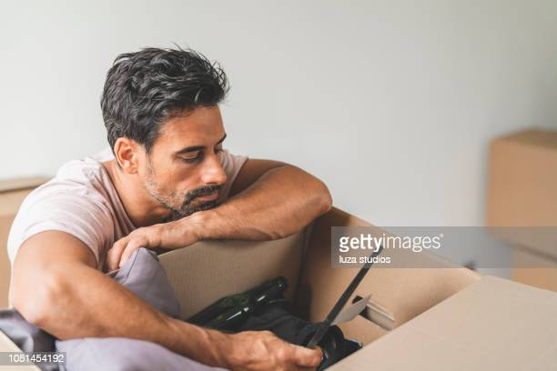 Man looking at old pictures while moving into a new house